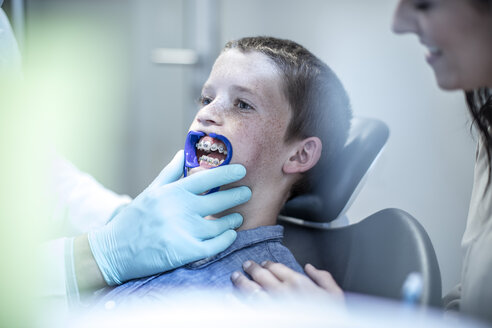 Boy with mother in dental surgery receiving orthodontic treatment - ZEF10627