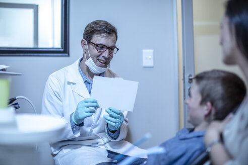 Smiling dentist holding paper with boy and mother in dental surgery - ZEF10633
