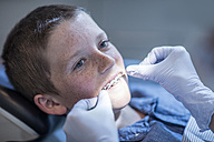 Boy with braces in dental surgery receiving dental floss treatment - ZEF10651