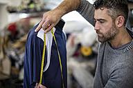 Tailor measuring sports shirt on mannequin in workshop - ZEF10660