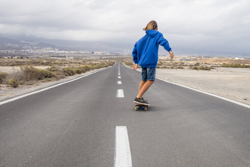 Spain, Tenerife, back view of boy skateboarding on empty country road - SIPF00940