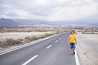 Spain, Tenerife, boy walking on empty country road - SIPF00943