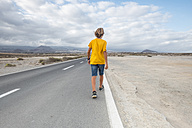 Spain, Tenerife, back view of boy walking on empty country road - SIPF00946