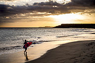 Spain, Tenerife, boy carrying surfboard on the beach at sunset - SIPF00952