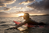 Spain, Tenerife, boy surfing in the sea at sunset - SIPF00964