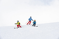 Father and two sons skiing together - HHF05451
