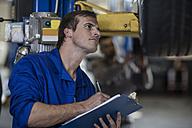 Car mechanic holding clipboard examining car in repair garage - ZEF10703