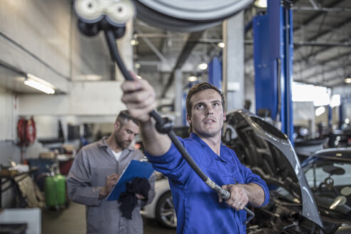 Car mechanic in a workshop pulling on hose machine - ZEF10709