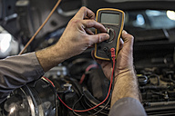 Close-up of car mechanic in a workshop using diagnostic equipment - ZEF10712