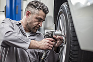 Car mechanic in a workshop changing tire - ZEF10715