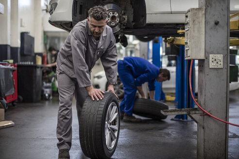 Car mechanics in a workshop changing tires - ZEF10718