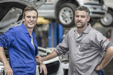 Two confident car mechanics in repair garage - ZEF10727