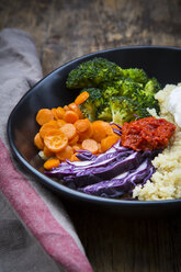 Lunch bowl of quinoa, red cabbage, carrots, roasted chickpeas, broccoli, poached egg and ajvar - LVF05481