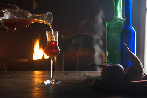 Hand pouring liqueur into shot glass in front of open fire - HHF05455