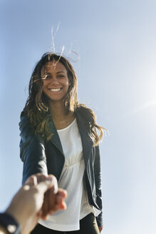 Portrait of smiling young woman with long brown hair in front of sky - MGOF02528