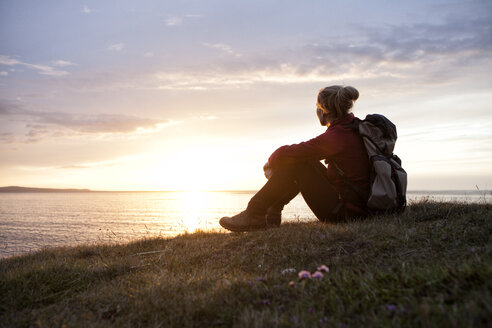 Iceland, hiker sitting on a meadow looking at view by twilight - RBF05213