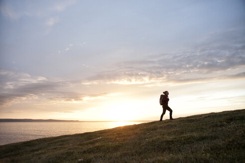 Iceland, woman hiking upon a hill at twilight - RBF05216