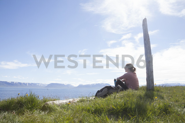 Iceland, hiker resting on a meadow looking at view - RBF05225 - Rainer Berg/Westend61