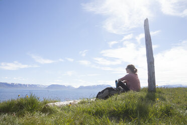 Iceland, hiker resting on a meadow looking at view - RBF05225