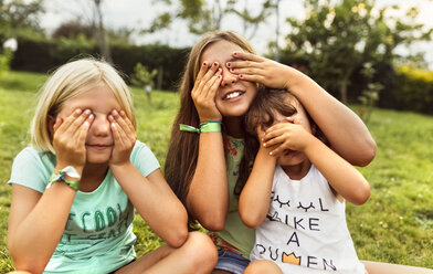 Three girls covering eyes with their hands on a meadow - MGOF02542