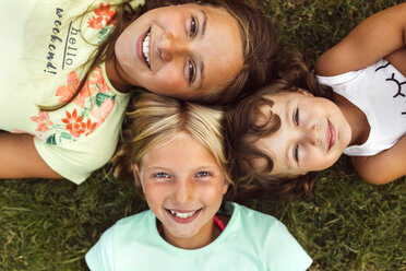 Three smiling girls lying head to head  on a meadow - MGOF02545