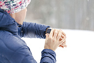 Sportive man checking his smartwatch in winter - MMAF00001