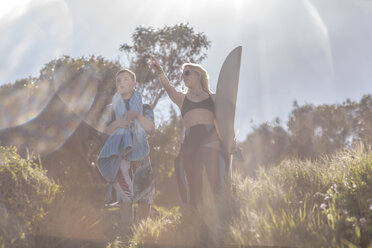 Teenage boy with down syndrome and woman with surfboard at the coast - ZEF10861