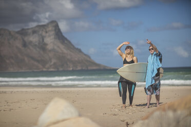 Teenage boy with down syndrome and woman with surfboard on beach - ZEF10864
