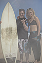 Teenage boy with down syndrome and woman with surfboard on beach - ZEF10867