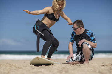 Teenage boy with down syndrome having surf lessons on beach - ZEF10870