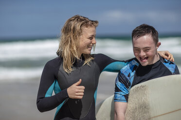 Happy teenage boy with down syndrome and woman with surfboard on beach - ZEF10873