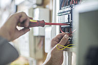 Electrician working on wired electrical board - ZEF10894