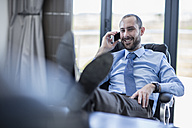 Smiling businessman sitting at his desk, talking on the phone - ZEF10960