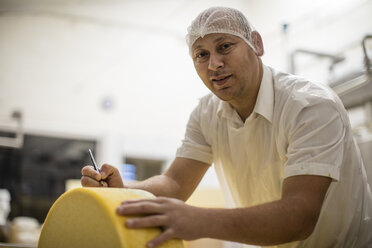 Cheese factory worker labelling cheese wheel - ZEF11011