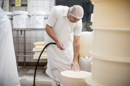 Cheese factory worker cleaning containers with hose - ZEF11017