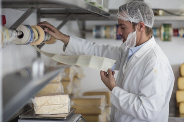 Cheese factory worker weighing packaged cheese - ZEF11047