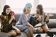 Three young women sitting on the couch wearing bathrobes preparing for the day - LCUF00066