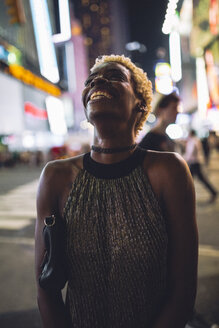 USA, New York City, smiling young woman on Times Square at night looking up - GIOF01571