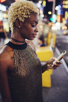 USA, New York City, young woman on Times Square at night looking at smartphone - GIOF01574