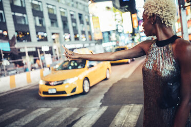 USA, New York City, young woman hailing a taxi on Times Square at night - GIOF01580