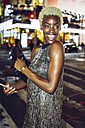 USA, New York City, portrait of happy young woman on Times Square at night - GIOF01583