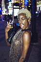 USA, New York City, young woman pulling funny faces on Times Square at night - GIOF01586