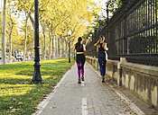 Two young women jogging on pavement - EBSF01783