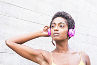 Portrait of woman listening music with pink headphones - SIPF00970