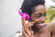 Portrait of happy woman listening music with pink headphones - SIPF00973
