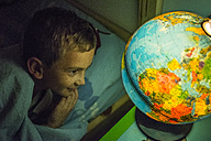 Smiling little boy in bed looking at globe - LOM00428