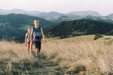 Italy, Gubbio, two children hiking at Apennine Mountains in the evening - LOMF00440