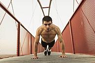 Young shirtless man doing push-ups on bridge - JASF01254