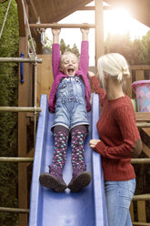 Happy little girl on a slide watching her mother - MIDF00797