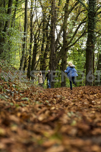 Happy family relaxing in autumnal forest - MIDF00800 - Miriam Dörr/Westend61